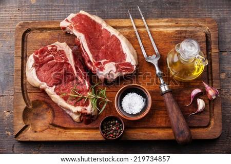 Raw fresh meat Ribeye Steak, seasoning and meat fork on dark background - stock photo