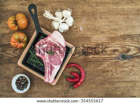 Raw fresh meat ribeye steak with pepper, salt, chili, garlic, heirloom tomatoes and rosemary in cooking pan over rustic wooden background, top view, copy space - stock photo