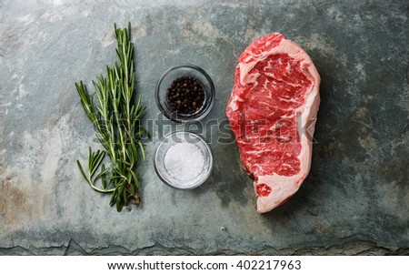 Raw fresh meat steak Striploin with rosemary, salt and pepper on stone slate background - stock photo