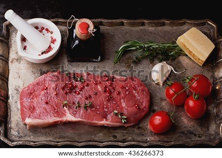 Raw fresh meat Striploin steak and seasoning on a rustic metal tray over dark metal background, top view - stock photo
