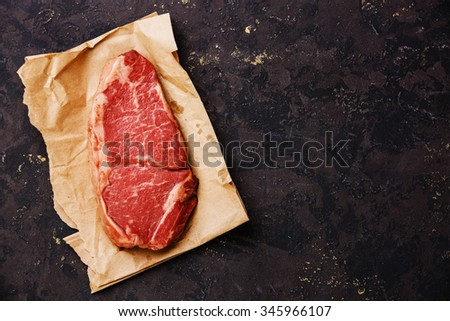 Raw fresh meat Striploin steak on kraft paper background - stock photo