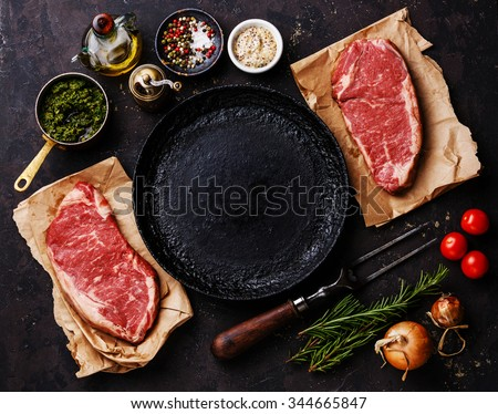 Raw fresh meat Striploin steaks with ingredients around frying pan on dark background - stock photo