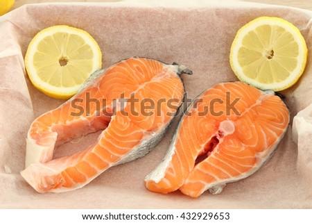 Raw fresh salmon steaks on baking paper - stock photo