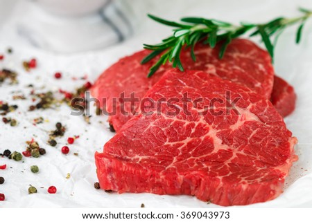 Raw fresh steaks from the marble beef, rosemary and spices on the table. Selective focus - stock photo