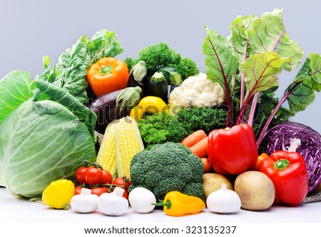 Raw fresh vegetables from the farmers market, broccoli, cabbage, beetroot, mushroom, tomato, garlic, squash, sweetcorn isolated on light grey background  - stock photo