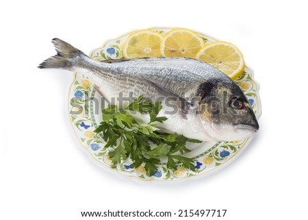 Raw gilt-head sea bream fishes garnished with parsley and lemon slices isolated on a white background - stock photo
