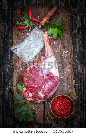 Raw goat or lamb leg with spices, ready for roasting - stock photo