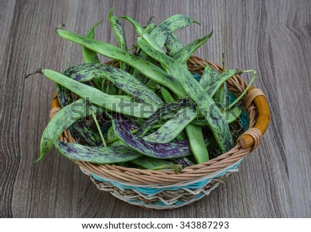 Raw green beans in the basket on the wood background - stock photo