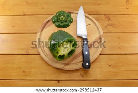 Raw green pepper sliced open with a sharp kitchen knife on a wooden chopping board, focus on the seeds and membrane inside - stock photo