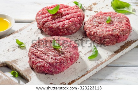 Raw Ground beef Burger steak patties on a white wooden cutting board. Selective focus - stock photo