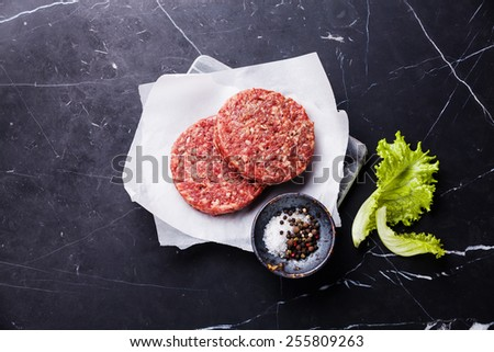 Raw Ground beef meat Burger steak cutlets and seasonings on dark marble background - stock photo