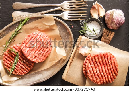 Raw Ground beef meat Burger steak cutlets on  wooden background. Flat Lay. Top view. - stock photo