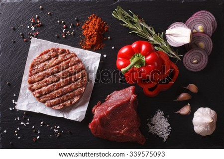 Raw Ground beef meat Burger steak cutlets with ingredients on the board. horizontal view from above closeup  - stock photo