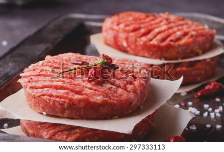 Raw Ground beef meat Burger steak cutlets with seasoning on vintage metal tray, black background - stock photo