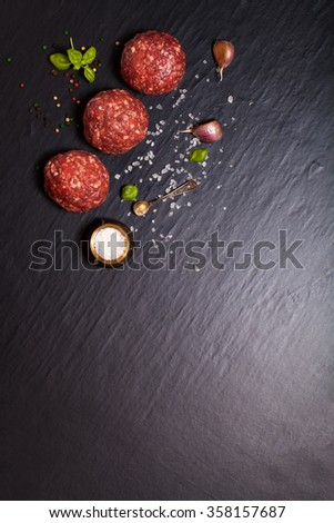 Raw ground beef meat steak cutlets with herbs and spices on black table or board for background. Selective focus. - stock photo