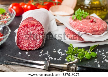 Raw Ground meat Burger and salami with seasonings, tomato and olive oil on slate background - stock photo
