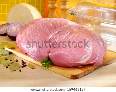 Raw ham on cutting board and glass baking pan. Pork meat in the kitchen. - stock photo