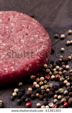 raw hamburger on a wooden board with spices - stock photo