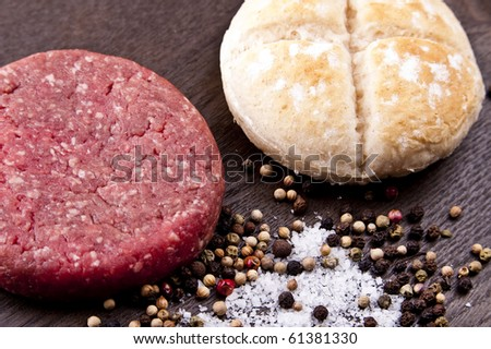 raw hamburger on a wooden board with spices and burger bun - stock photo