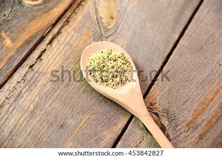 Raw hemp seeds on spoon on rustic wooden table - stock photo
