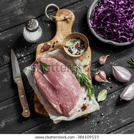 Raw ingredients - meat, red cabbage, onion, garlic, spices and herbs. Cooking delicious and healthy lunch. On wooden rustic background - stock photo