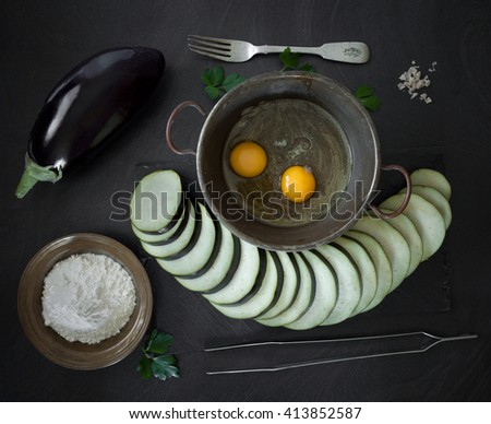 Raw ingredients necessary to prepare fried eggplant: eggs, flour, salt and eggplants. - stock photo