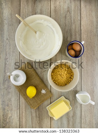 Raw ingredients to make a classic new york baked cheesecake with lemon, on burlap and weathered boards. - stock photo