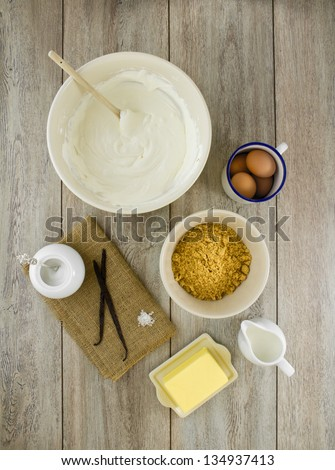 Raw ingredients to make a classic new york baked cheesecake with vanilla on burlap and weathered boards. - stock photo