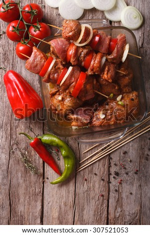 raw kebab with vegetables in a spicy marinade on skewers on the table. vertical top view