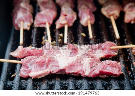 Raw kebabs skewers on the grill being cooked - stock photo