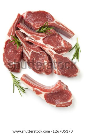 Raw lamb cutlets with rosemary sprigs, isolated on white. - stock photo
