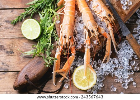 Raw langoustines on ice with herbs and lemon served on vintage cutting board over wooden table. Top view. - stock photo