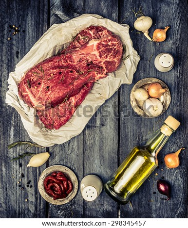 Raw marbled beef meat with ingredients for cooking on rustic wooden background, top view. Retro toned. Frame. - stock photo
