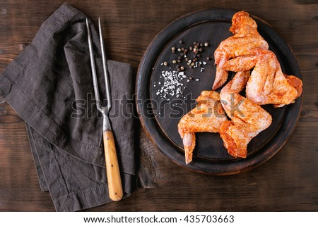 Raw Marinated chicken meat wings for BBQ, served on round wood chopping board with seasoning and vintage meat fork on textile over dark wooden background. Top view with copy space. - stock photo