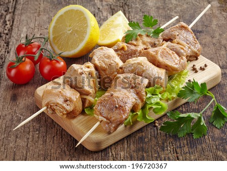 raw marinated pork kebab meat pieces on wooden skewers - stock photo