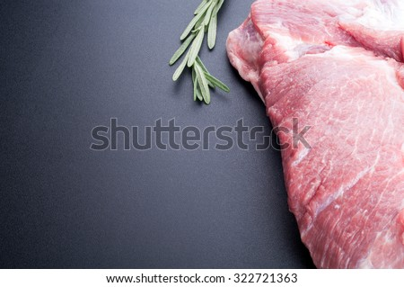 Raw meat and rosemary on dark background. Lots of copy space. Selective focus - stock photo