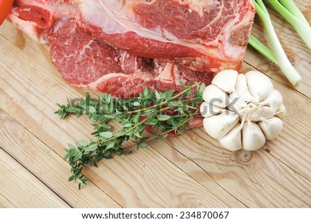 raw meat : boned fresh lamb ribs served with thyme , garlic and red chili pepper on wooden board - stock photo