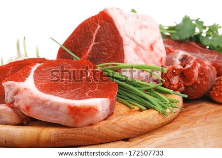 raw meat : fresh beef pork big rib and fillet with garlic and green stuff on wood isolated over white background - stock photo