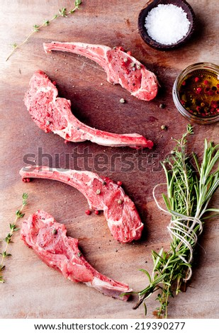 Raw meat, mutton, lamb rack with fresh herbs on a white paper background - stock photo