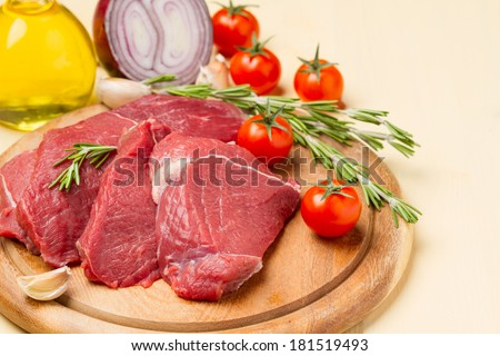 Raw meat on round board, tomatoes, onions, oil and rosemary - stock photo