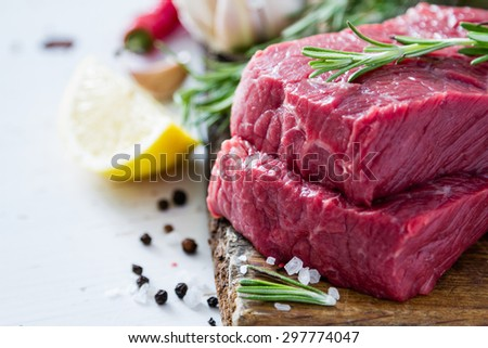 Raw meat, rosemary, salt, pepper, garlic, lemon, wood background - stock photo