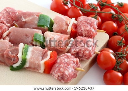 Raw meat skewers with cherry tomatoes - stock photo