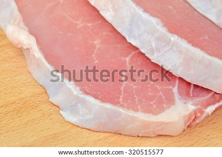 Raw meat steaks on wooden board background, DOF - stock photo