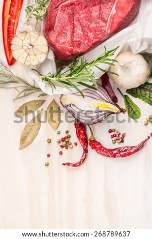 Raw meat with herbs and spices: bay leaf, garlic, pepper  on white wooden background, top view, close up, place for text - stock photo