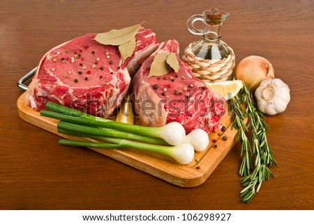 raw meat with rosemary, onion, garlic, peppercorn, lemon and oil - stock photo