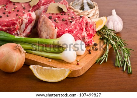 raw meat with rosemary, onion, peppercorn, lemon and oil, close-up - stock photo