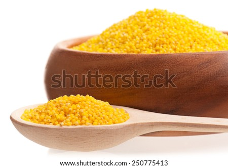 Raw millet grains in the bamboo bowl isolated on white background. Focus on the spoon - stock photo