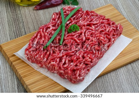 Raw minced beef with onion and parsley - ready for cooking - stock photo