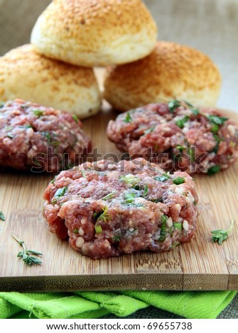raw minced meat for hamburgers on a wooden board - stock photo