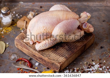 Raw mini Chicken on wooden cutting board with sea salt and different spices over old metal surface - stock photo